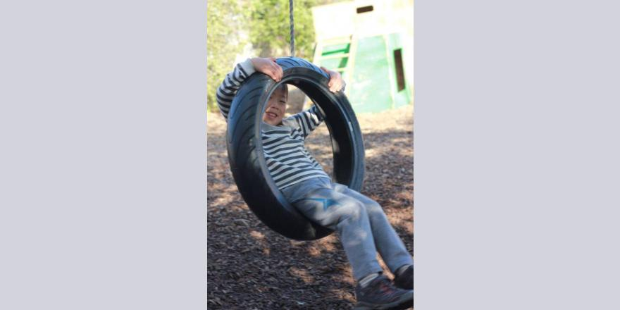 Boy in tyre swing at Annabel's Avonhead preschool