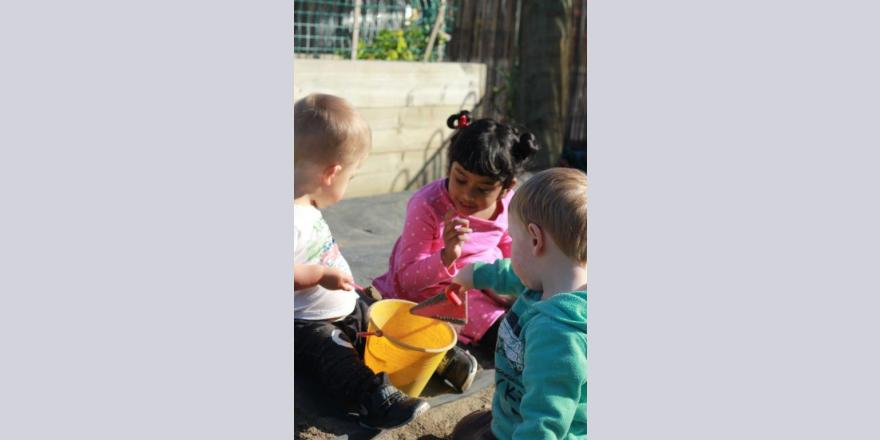 Kids playing with bucket of sand at Annabel's Avonhead preschool