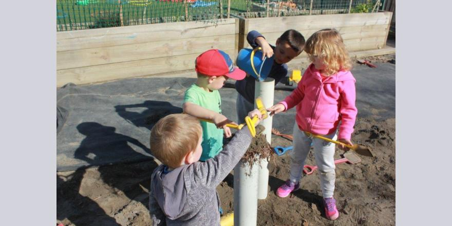 Children at Annabel's Avonhead preschool building sand structures in the sandpit