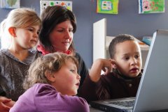 Kids gathered around the preschool teacher and laptop